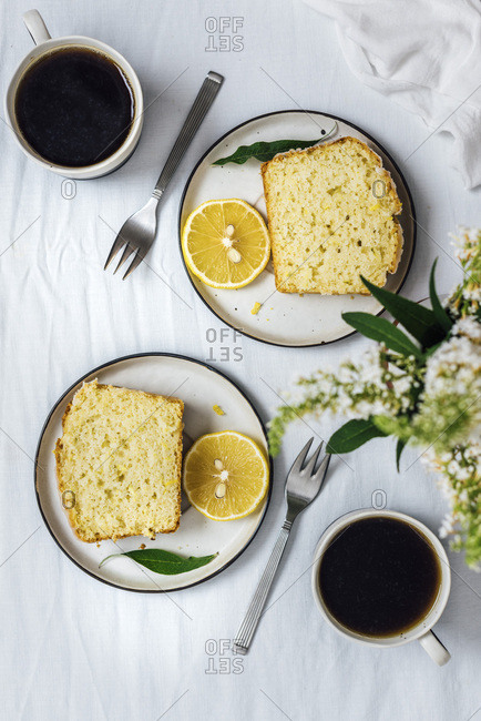 Lemon zucchini bread slices served on two plates with a lemon slice on the side. Two cups of coffee, two forks and flowers in a vase accompany