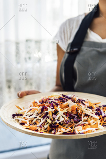 A woman with a white T-shirt and a grey apron holding a wooden bowl with coleslaw made with shredded carrot, white and purple cabbage photographed from front view