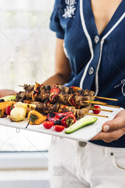 A woman serving lamb shish kebabs with grilled peppers, shallots, fresh cherry tomatoes and cucumber on a white marble board photographed from front view