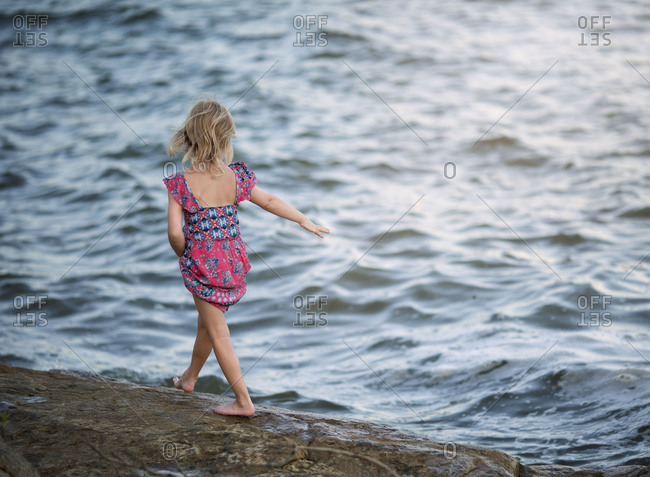Girl walking barefoot along shore