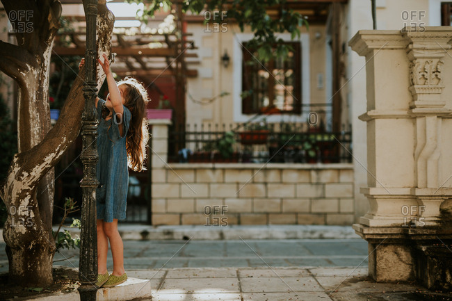 Girl climbs a tree on the street