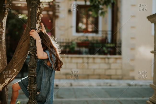 Girl climbing a slender tree