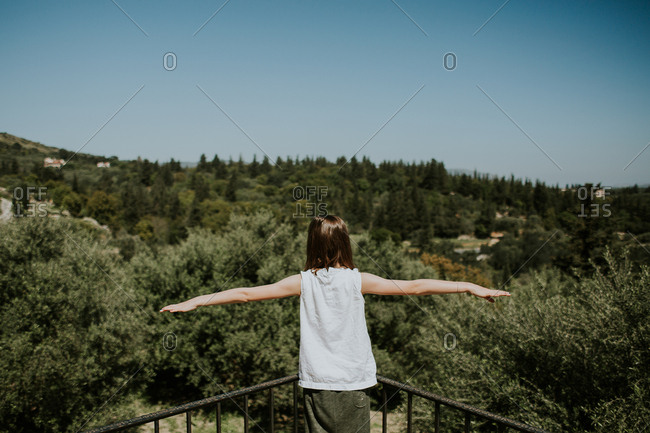 Girl standing on balcony with arms spread