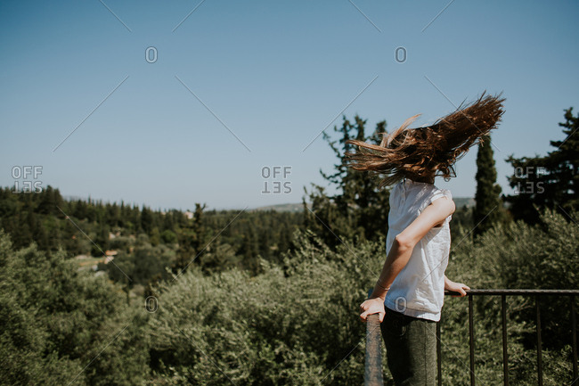 Girl shakes her hair on balcony