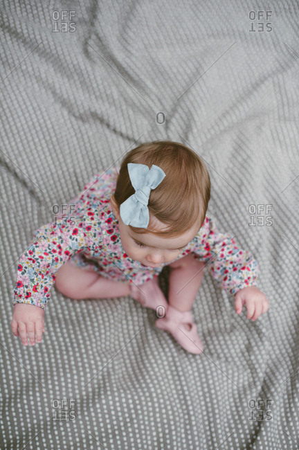 Girl on blanket with bow in hair