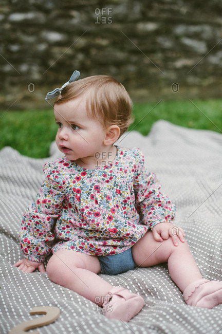 Girl staring off on blanket outdoors