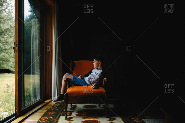 Boy lounging across chair gazing out door