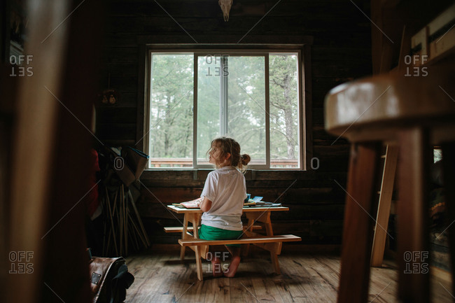 Child sitting at small table in cabin