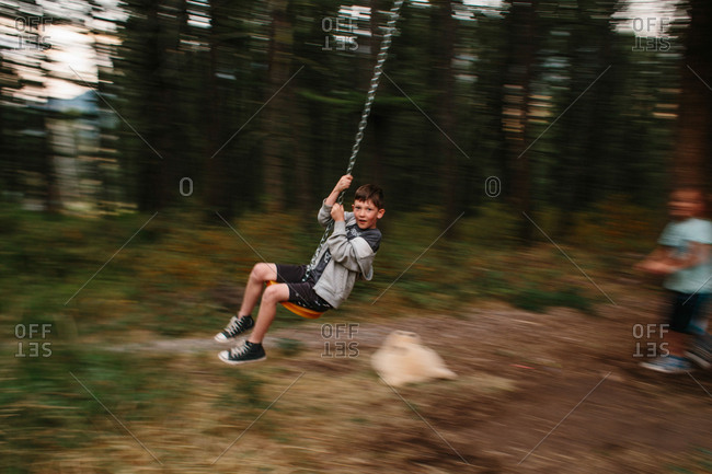 Boys on swing in motion blur