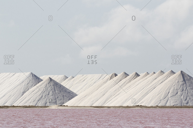 Mountains of salt collected in salt pans by the Cargill Salt Works with pink water in the flats caused by high concentrations of salt-loving bacteria