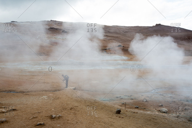A man looks at and photographs the steaming mud pots geothermal area near Lake Myvatn