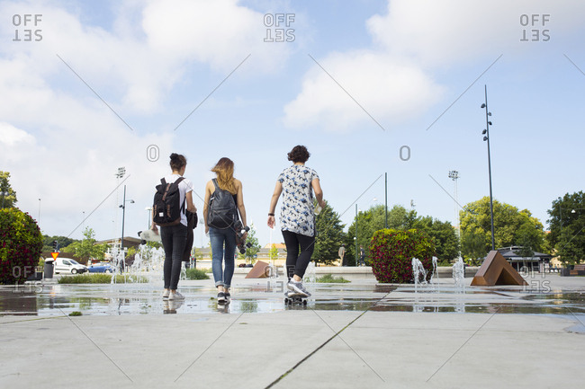 Rear view of teenage girls (14-15) and teenage boy (16-17) hanging out in skateboard park