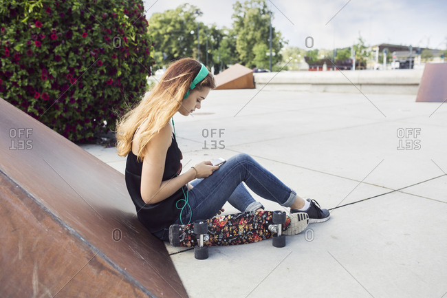 Teenage girl (14-15) sitting in skateboard park and listening to music