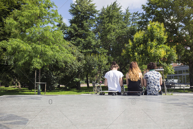 Rear view of teenage girls (14-15) and boy (16-17) sitting in skateboard park