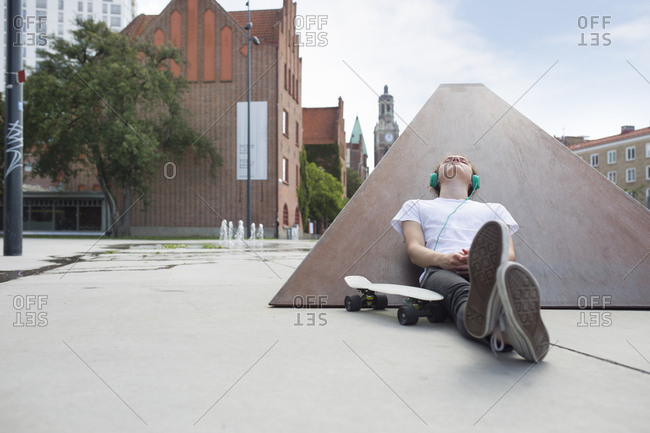 Teenage boy (16-17) sitting in skateboard park and listening to music