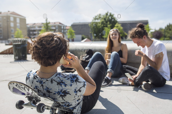 Teenage girls (14-15) and teenage boy (16-17) hanging out in skateboard park