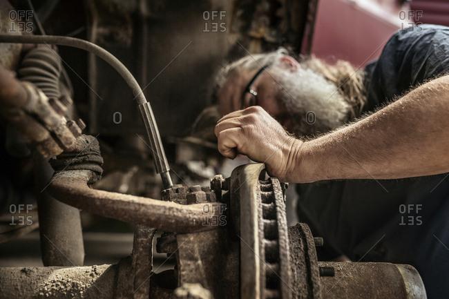 Mature man repairing car