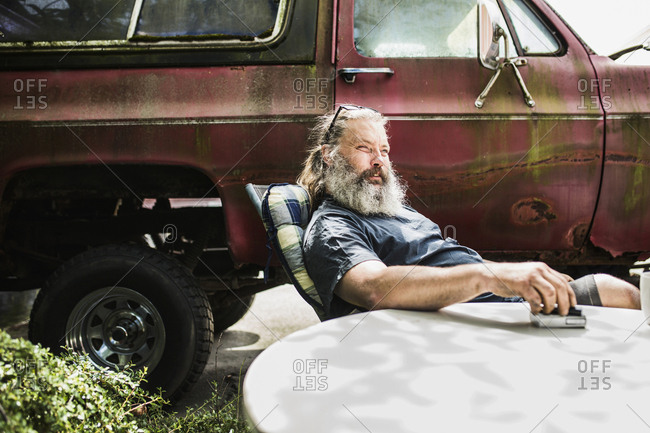 Portrait of mature man sitting by old car