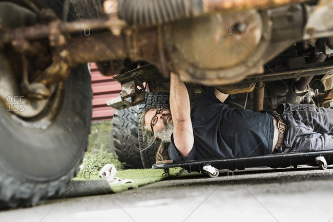 Mature man repairing car