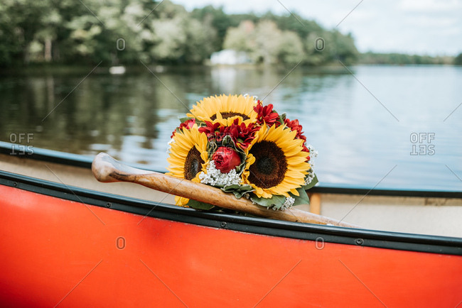 Bridal bouquet in a canoe on a lake