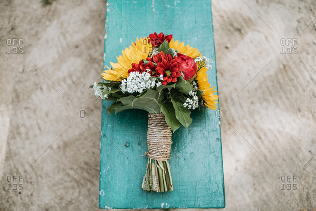 Bridal bouquet on a green wooden bench