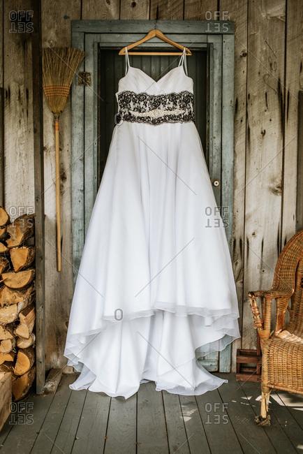 Bridal gown hanging on door to rustic cabin