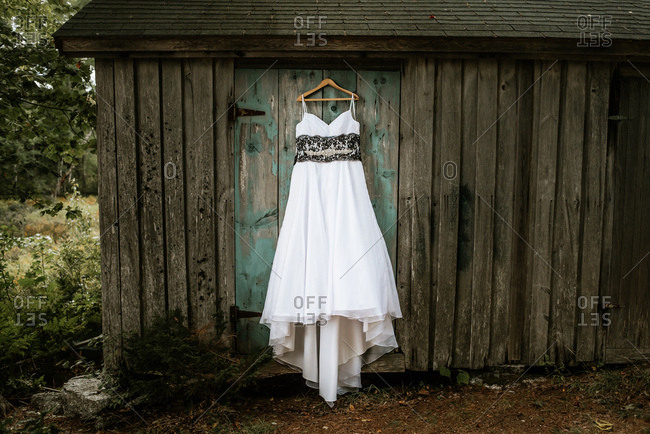 Bridal gown hanging on old barn door