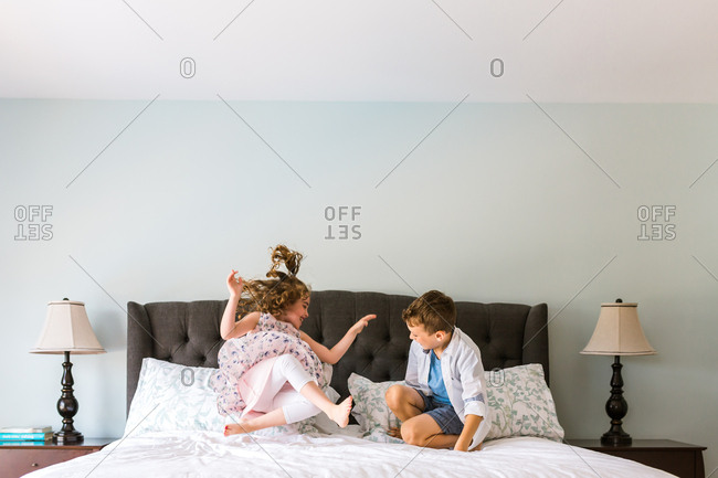 Two kids jumping on a bed