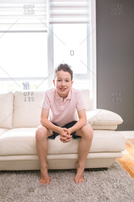 Smiling barefoot boy sitting on sofa