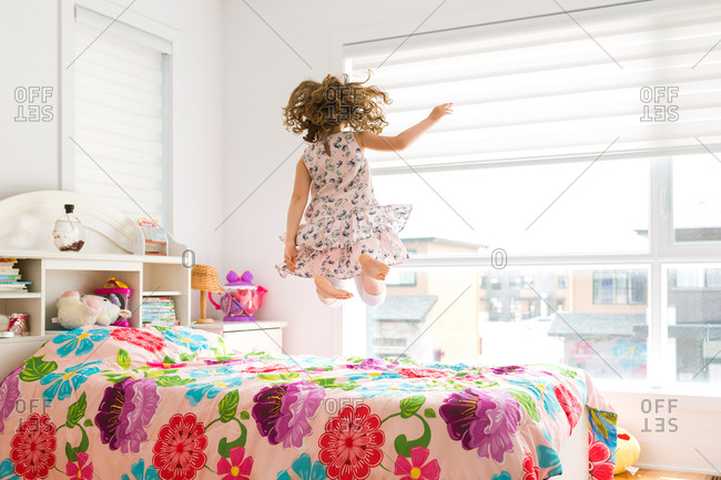 Rear view of girl jumping on her bed