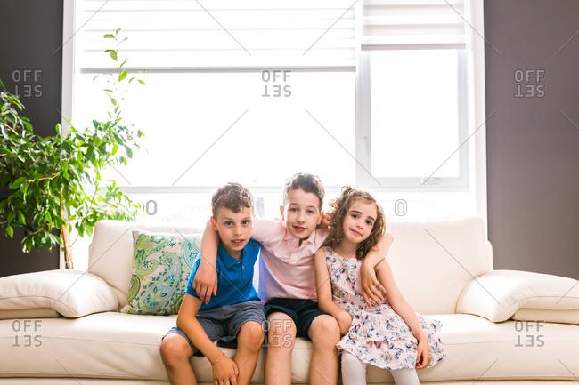 Three kids sitting together on sofa