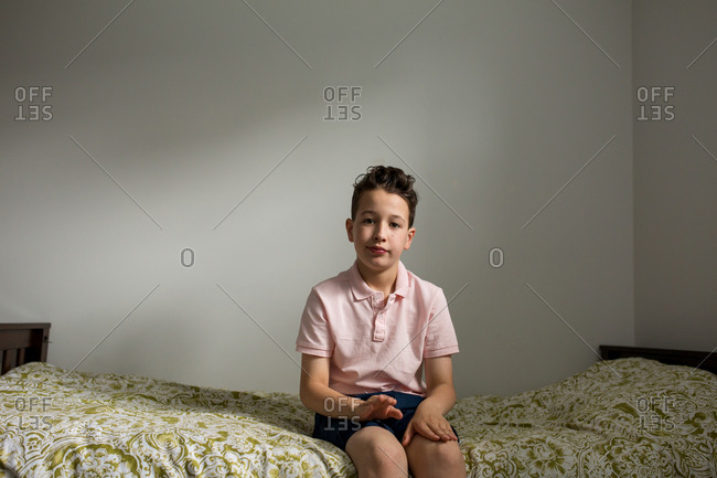 Boy sitting on bed tapping his knees