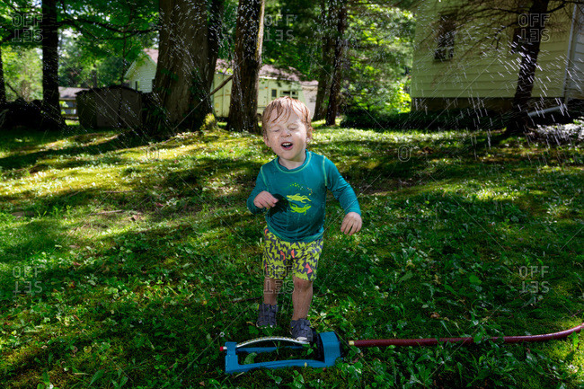 Toddler runs through a lawn sprinkler on a summer day