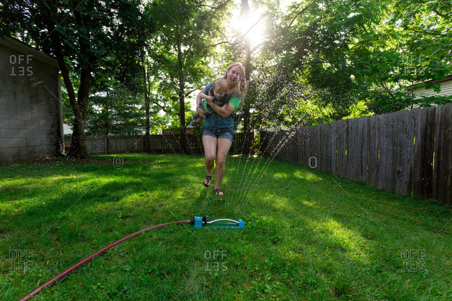 Mother and her toddler run through a backyard sprinkler on a summer day
