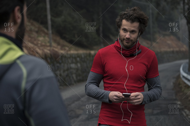 Jogger with device looking at friend