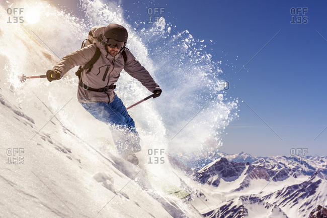 Front view of descending skier in ski mountaineering in fresh powder with backpack on snow covered wild mountain