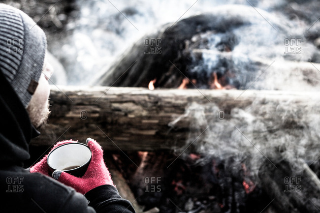 Man with hot drink by fire