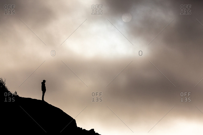 Person silhouetted on hill near sun