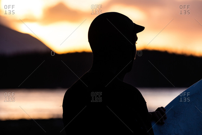 Surfer in silhouette near shore