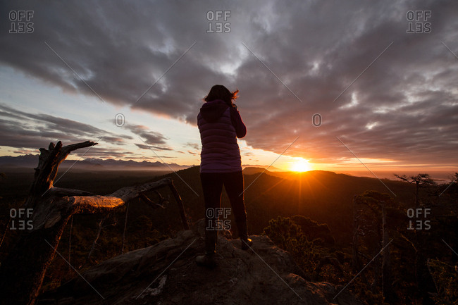 Woman in sunlight on mountain top