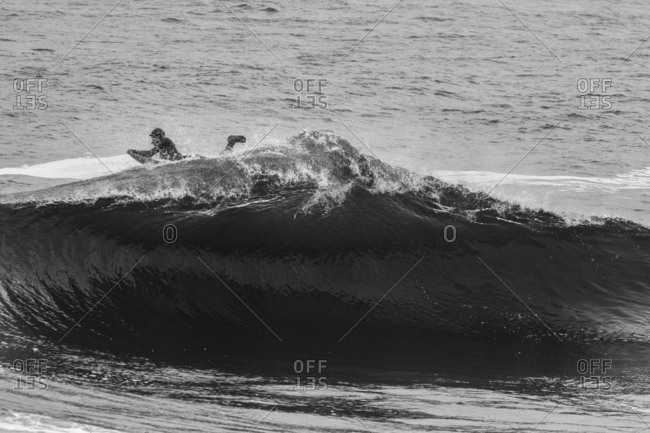 A surfer paddling on wave
