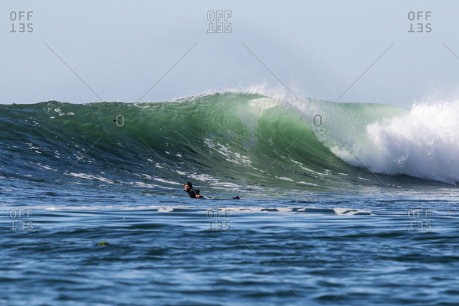 Surfer paddling near cresting wave