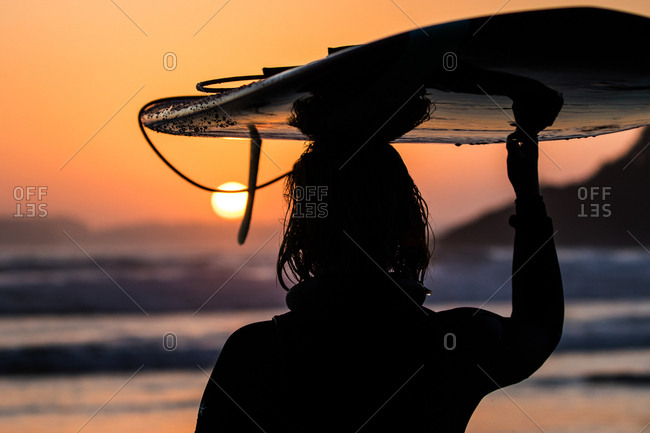 Surfer silhouetted holding board