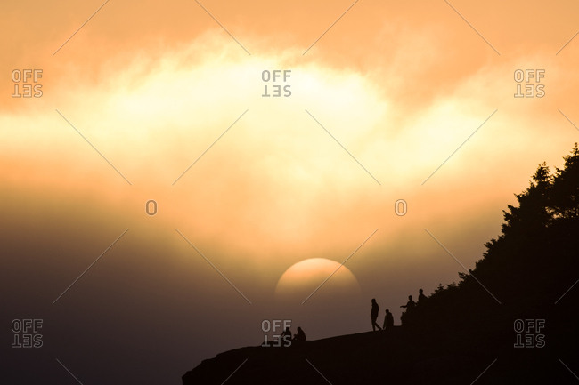 People silhouetted by sun on hill