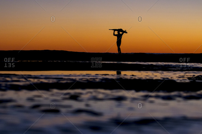 Surfer silhouetted by glowing sky