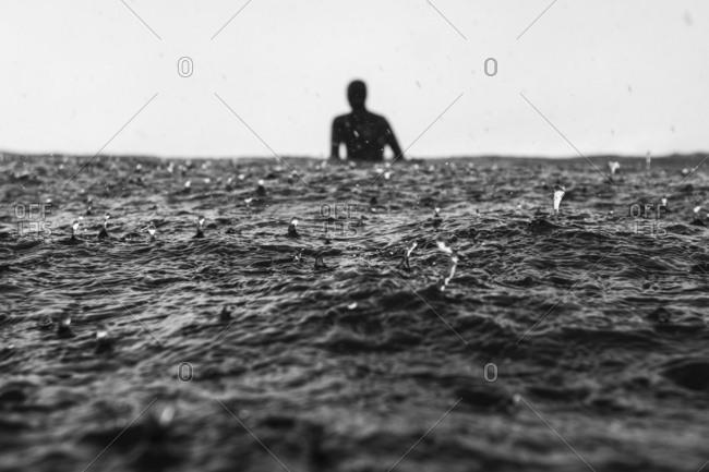 Surfer by rain drops on sea