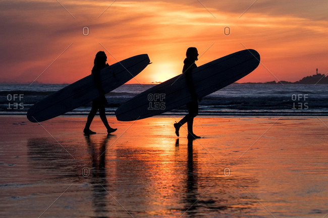 Surfers silhouetted by a glowing sky
