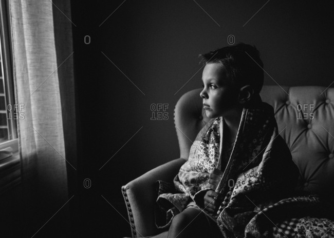 Boy sitting on chair wrapped in a quilt