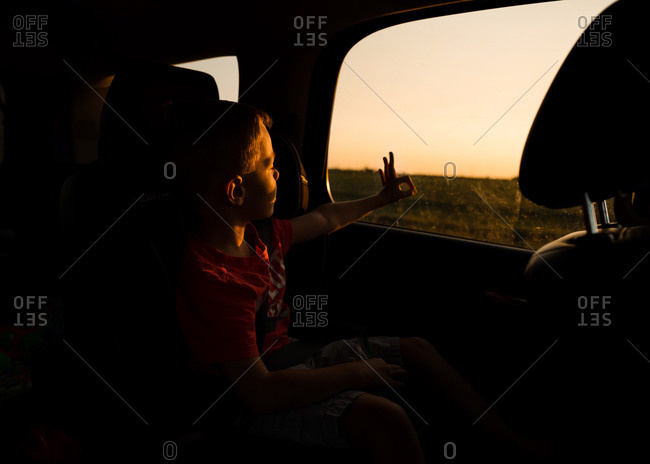 Boy riding in car and looking at the sun through a circle with his fingers