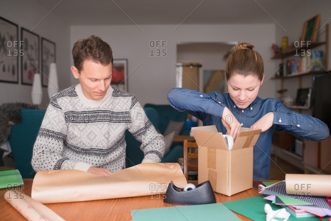 Couple wrapping holiday gifts